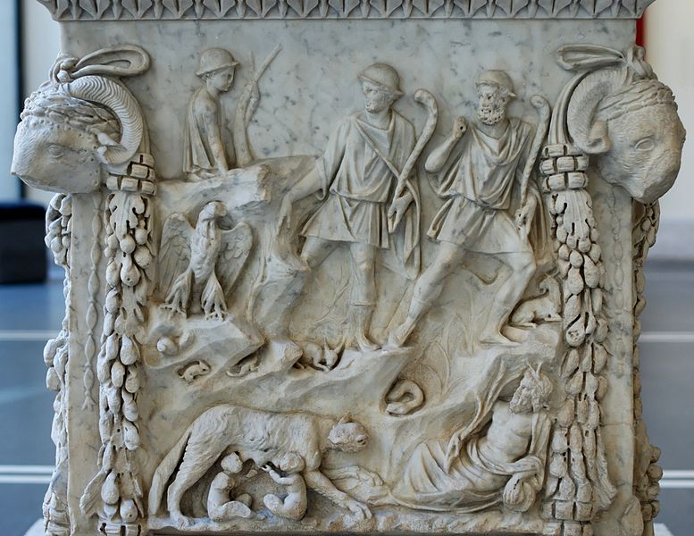 Representation of the lupercal: Romulus and Remus fed by a she-wolf, surrounded by representations of the Tiber and the Palatine. Panel from an alter dedicated to the divine couple of Mars and Venus. Marble, Roman artwork of the end of the reign of Trajan (98-117 CE), later re-used under the Hadrianic era (117-132 CE) as a base for a statue of Silvan. From the portico of the Piazzale dei Corporazioni in Ostia Antica.